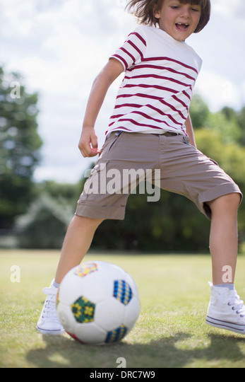 Boy playing soccer outdoors - Stock Image