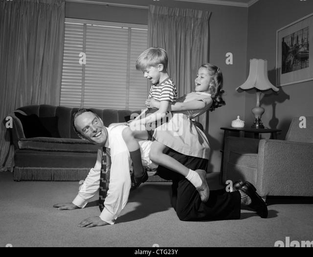 1950s 1960s DAD CARRYING BOY & GIRL PIGGYBACK ON LIVING ROOM FLOOR - Stock Image