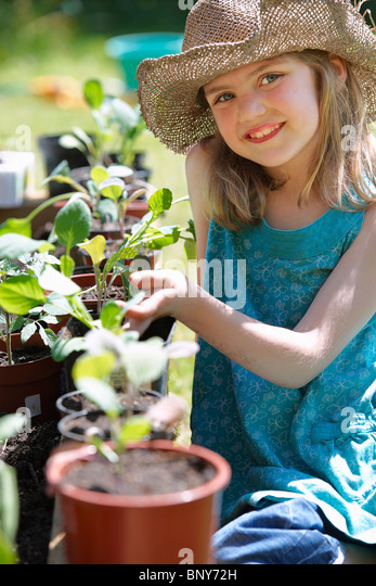 Young Girl looking at vegetable plants - Stock Image