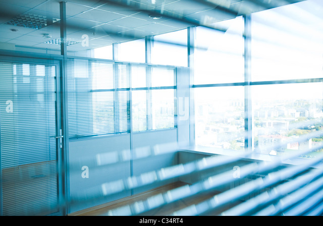 Image of corridor in office building with big windows passing daylight - Stock Image