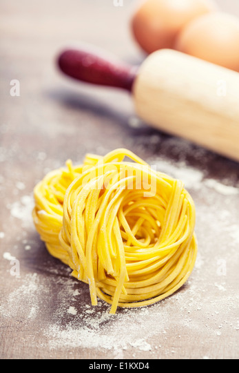 Making homemade pasta on wooden table - Stock Image