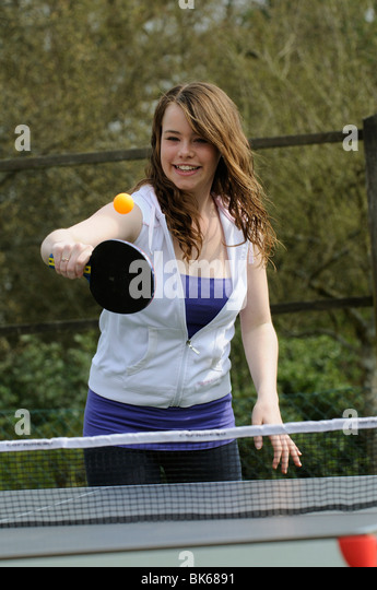 Teenager girl playing a game of table tennis in her garden - Stock Image