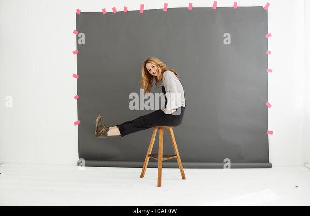 Woman on stool in front of photographers backdrop - Stock Image