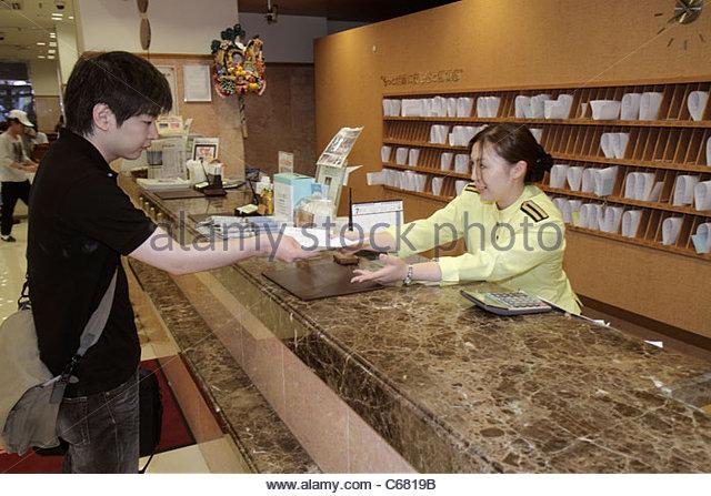 Tokyo Japan Ikebukuro Toyoko-Inn Ikebukuro Kita-guchi No.2 hotel lobby front desk clerk uniform guest Asian man - Stock Image