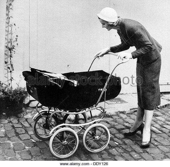 Woman peering into a pram, 1950s. - Stock-Bilder