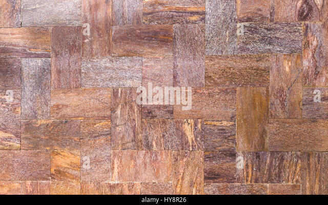 A wall of stone tiles or brick, classic example of exterior wall decoration or background - Stock Image