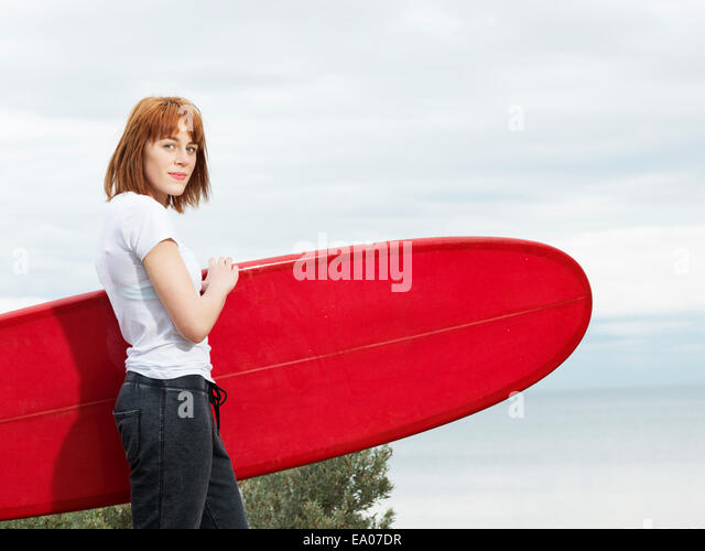 Female surfer with longboard surfboard, Williamstown beach, Melbourne, Australia - Stock Image