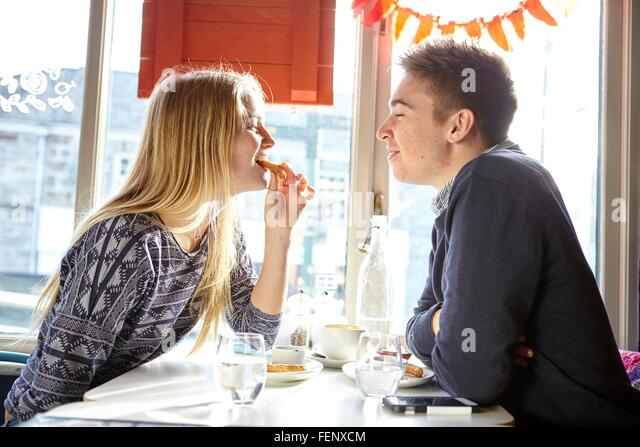 Romantic young couple lunching in cafe window seat - Stock-Bilder