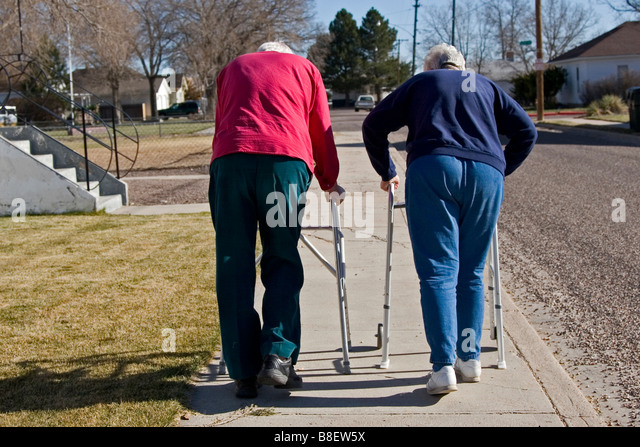 Two elderly senior citizens walk away using walkers, one of four in series - Stock-Bilder