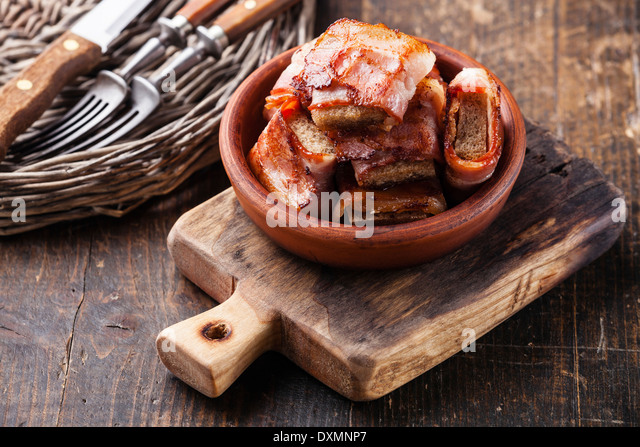 Appetizer bread slices fried in bacon - Stock Image