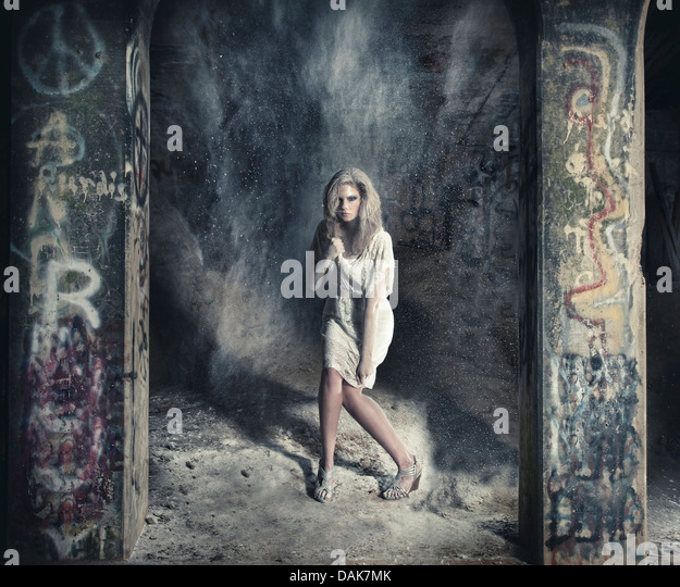 Woman standing between two graffiti covered columns covered in dust - Stock-Bilder