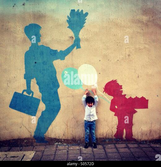 Little boy facing camera tries to reach for the balloon painted on the wall - Stock-Bilder