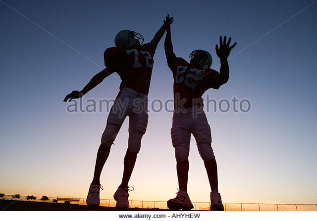 Two American football players celebrating on pitch at sunset, jumping up, doing high-fives backlit - Stock Image