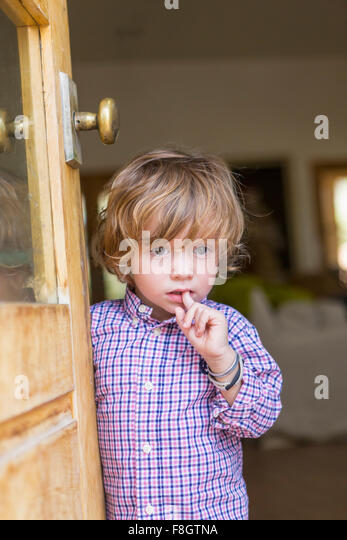 Caucasian boy looking out open door - Stock Image