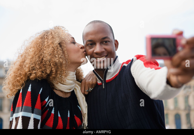 African couple taking own photograph - Stock-Bilder