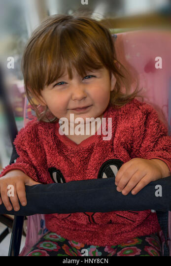 Blond baby girl sitting on a swing and wearing a pink fur sweater, while making a grimace at the camera. - Stock Image