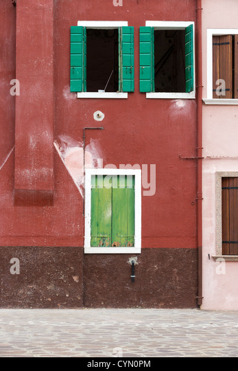 A reddish-brown painted house in Burano, Venice, with contrasting green shutters at the windows - Stock Image