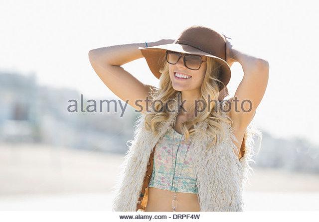 Portrait of woman wearing sunhat on beach - Stock Image
