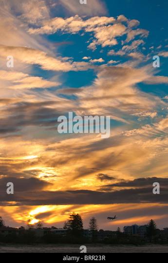 Commercial passenger jet landing under wispy clouds at sunset, Gold Coast Airport, Queensland, Australia - Stock Image