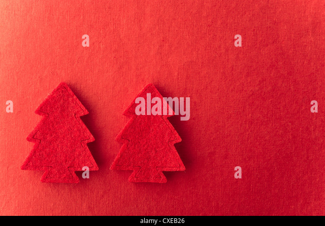 Christmas tree shapes on red background - Stock-Bilder