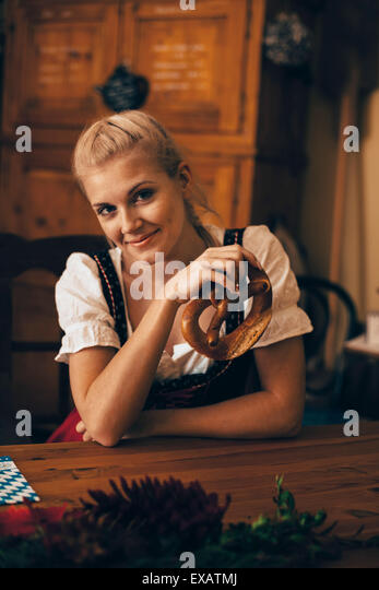 Woman sits at the table with Maß beer and pretzel - Stock Image
