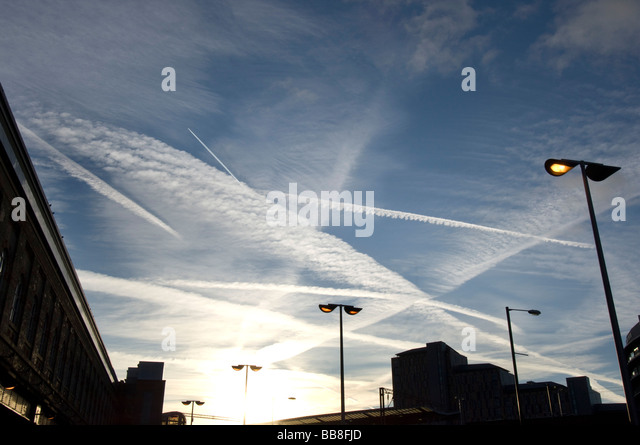 The jet trail from a jet aircraft leaves a trail in the sky as it soars through other jet streaks from other planes - Stock Image