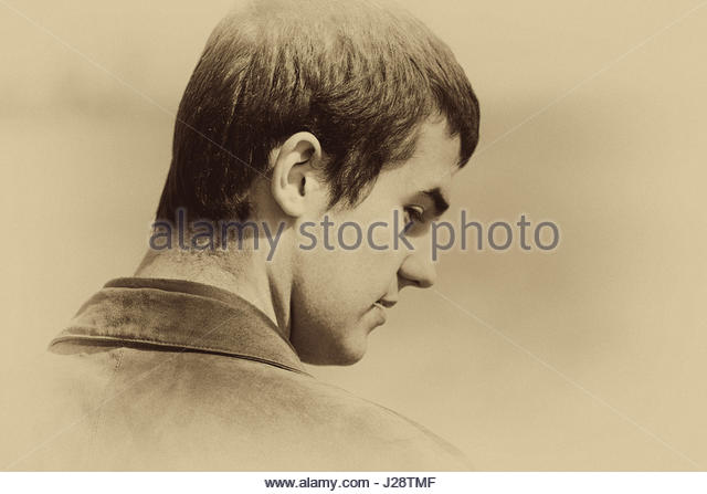 Young man looking over his shoulder - Stock Image