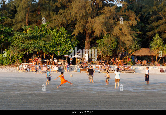 Kids playing soccer in front of J.J. Seafood Restaurant, Long Beach, Ao Yai, sunset, Koh Phayam, Thailand - Stock Image