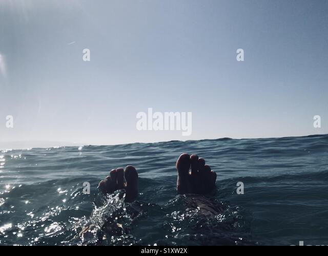 A persons feet in the water. Manhattan Beach, California USA. - Stock Image