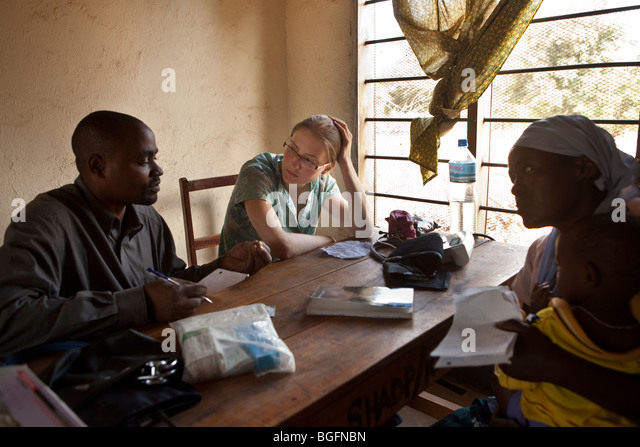 A western volunteer doctor consults patients in Tanzania. - Stock Image