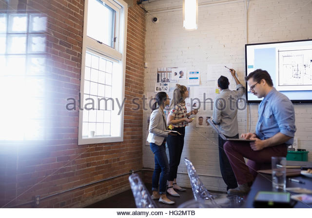 Designers meeting brainstorming reviewing proofs in conference room - Stock Image