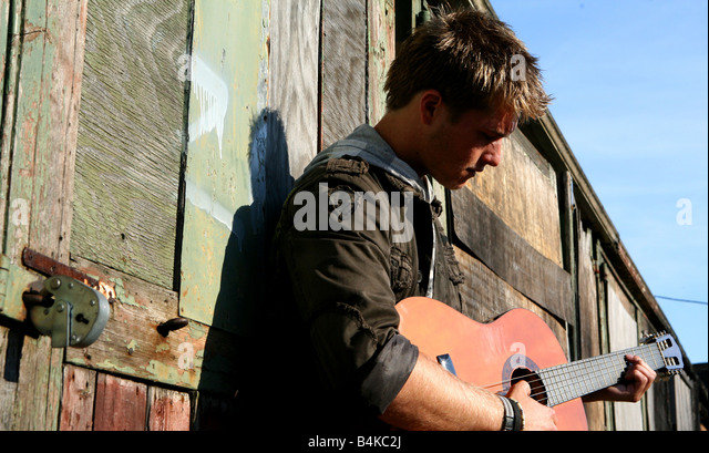 Man boy Playing Guitar down alley way busking - Stock-Bilder
