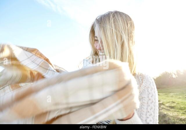 Young woman struggling with wind blown scarf - Stock Image