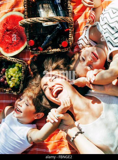 cute happy family on picnic laying on green grass mother and kids, warm summer vacations close up, brother and sister - Stock-Bilder