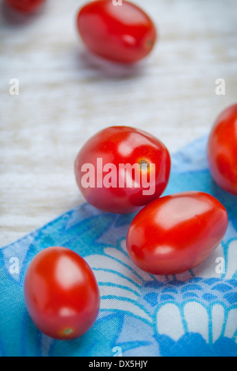 Close Up View of Grape Tomatoes on Blue Napkin - Stock Image