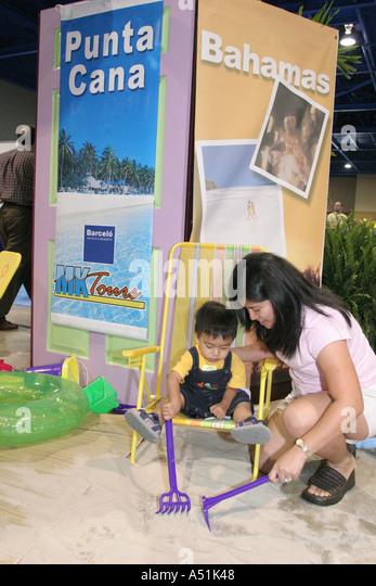 Coconut Grove Florida Convention Center Miami Herald Travel Expo Bahamas beach exhibit Hispanic family - Stock Image