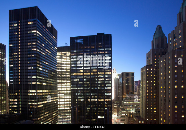 Buildings lit up at dusk in downtown Manhattan looking north with Waldorf Astoria, New York City, New York State, - Stock Image