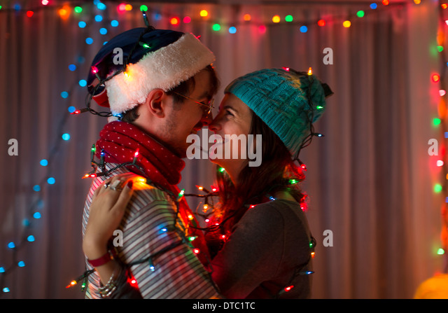 Romantic young couple wrapped in decorative lights at christmas - Stock Image