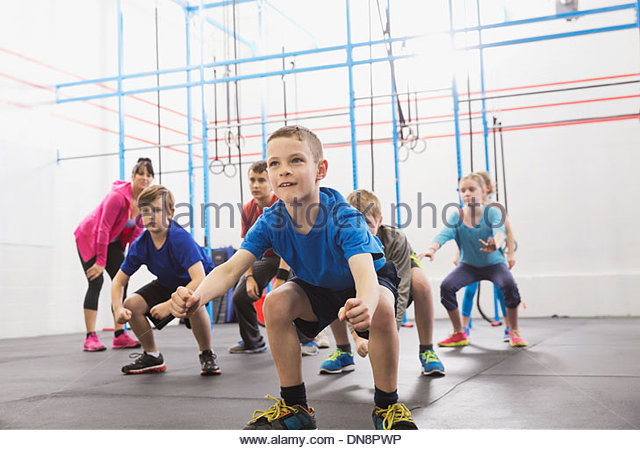 Kids practicing angry gorilla walk in Crossfit class - Stock Image
