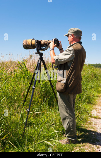 A bird photographer with a camera with a large lens on a tripod at Minsmere bird reserve , Suffolk , England , Britain - Stock Image