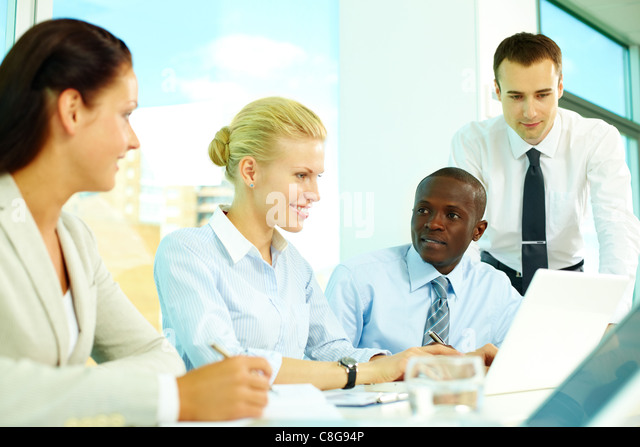 Four business people discussing affairs in office - Stock Image