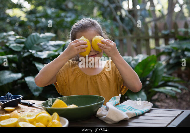 Girl holding lemons in front of eyes whilst preparing lemonade at garden table - Stock-Bilder