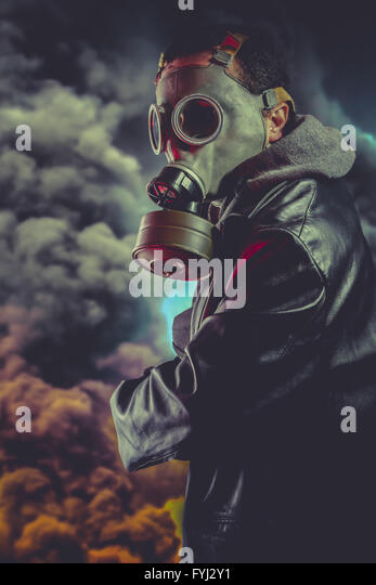 Armed man with gas mask over explosion background - Stock-Bilder