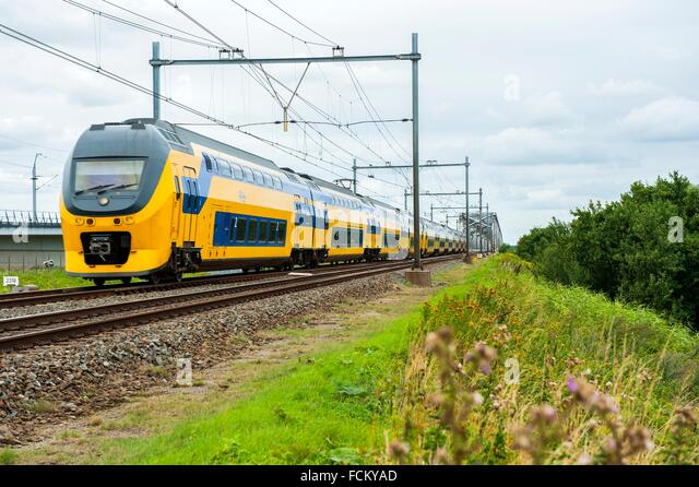 Moerdijk, Netherlands. Double deck intercity train passing the 1950´s build railroad bridge over ethe river - Stock-Bilder