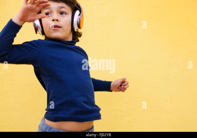 Dancing little boy in front of yellow wall hearing music with headphones - Stock Image