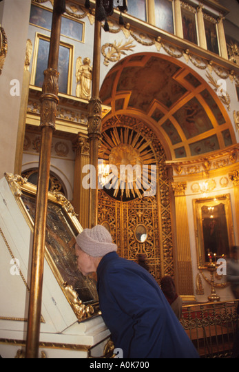 Russia former Soviet Union St. Petersburg Orthodox church interior woman kisses religious icon display case - Stock Image