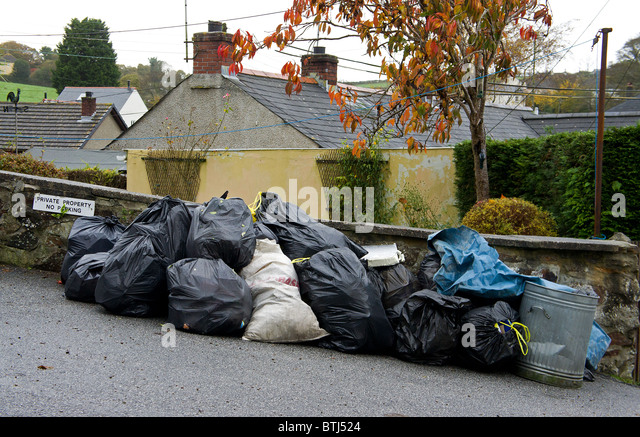 household waste on the roadside waiting to be collected by the local council refuse department, cornwall, uk - Stock Image