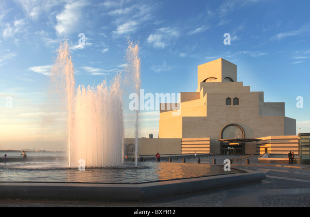 A view of the Museum of Islamic Art in Doha, Qatar, Arabia under a cloudy winter sky, with the water catching the - Stock Image