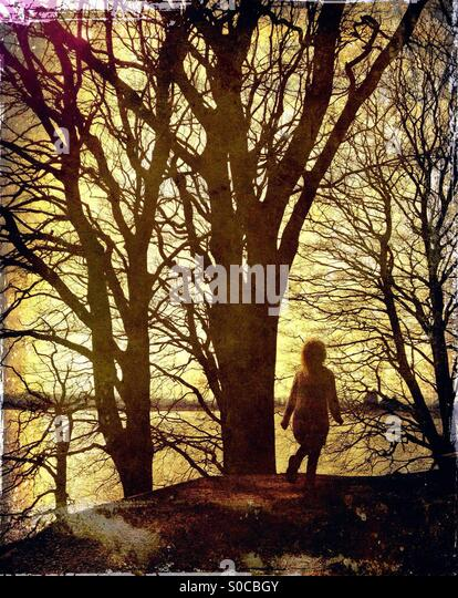 Girl walking along path with a background of tree silhouettes - Stock Image