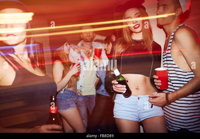 Young people with drinks relaxing at party in bar - Stock Image